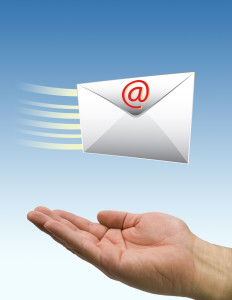 A hand receiving a letter via email