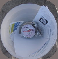 clock in waste paper bin