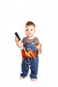 Young boy holding new tools and a mobile phone