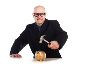 Angry man about to hammer a piggy bank.