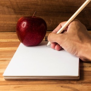 Apple resting on paper as a hand writes