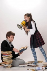 girl yelling through megaphone at boy reading