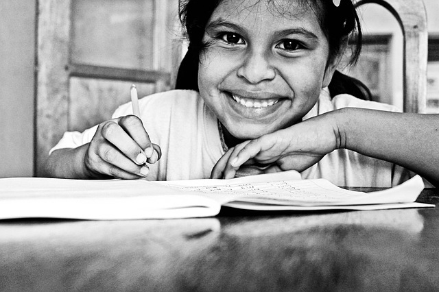 smiling girl writing in a book